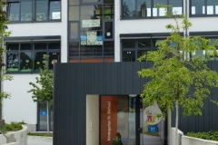 Neuer Kindergarten  mit sanierter Fassade der Grundschule im Hintergrund